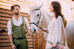 Nowożeńcy patrzeją each innego mienie konia fotografia royalty free