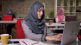 Nowożytna arabska kobieta pisać na maszynie na laptopie, patrzeje dokładnie przy ekranem, pracujący nastrój, siedzi przy miejsce