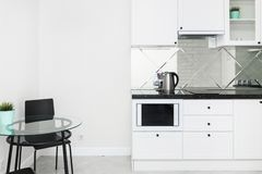 Nowożytna biała kuchnia w jaskrawym wnętrzu mieszkanie obraz stock