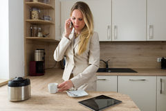 Nowożytna biznesowa kobieta z smartphone i kawą w kuchni Fotografia Stock
