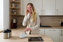 Nowożytna biznesowa kobieta z smartphone i kawą w kuchni Obrazy Royalty Free