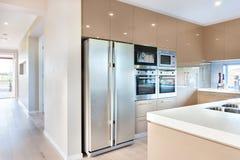Nowożytna chłodziarka w luksusowej kuchni z mikrofala piekarnikami zdjęcia stock