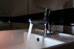 Nowożytna chrom instalacja wodnokanalizacyjna w ciemnej łazience zdjęcie stock