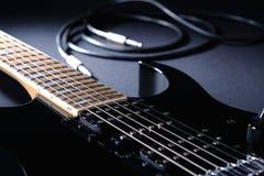 Nowożytna czarna gitara elektryczna z dźwigarka kablem na czerni obraz stock