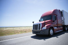 Nowożytna czerwieni semi ciężarówka i reefer przyczepa na drodze w słonecznym dniu obrazy stock