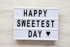Nowożytna deska z teksta ` dnia ` Szczęśliwym Sweetest słowem nad białą drewnianą powierzchnią, odgórny widok Od above, mieszkani zdjęcia stock