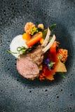 Nowożytna Francuska kuchnia: Zamyka w górę piec szyi słuzyć z marchewką Jagnięcego stojaka &, żółty curry słuzyć w czerń kamienia Zdjęcie Stock
