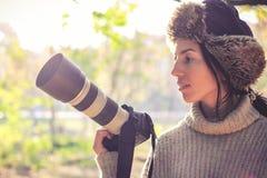 Nowożytna kamera z wielkim obiektywem w ręce młoda fotograf dziewczyna i przygotowywa brać fotografię zdjęcie royalty free