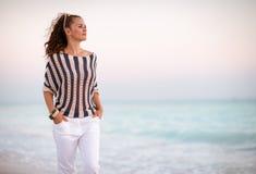 Nowożytna kobieta na seacoast w wieczór odprowadzeniu fotografia royalty free