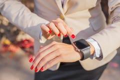 Nowożytna kobieta sprawdza czas na jej smartwatch zdjęcie royalty free