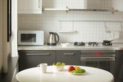 Nowożytna kuchnia, biały stół, kubek i zielona sałatka, Obrazy Stock