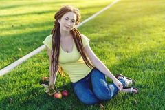 Nowożytna młoda dziewczyna z fryzury dreadlocks w parku na zielonej łące Cieszyć się jesień nastrój zdjęcia stock