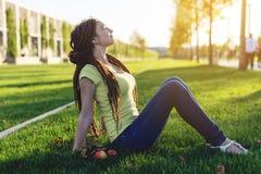 Nowożytna młoda dziewczyna z fryzury dreadlocks w parku na zielonej łące Cieszyć się jesień nastrój fotografia royalty free