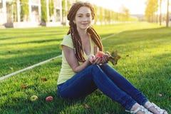 Nowożytna młoda dziewczyna z fryzury dreadlocks w parku na zielonej łące Cieszyć się jesień nastrój zdjęcie stock