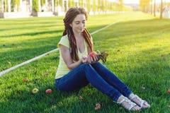 Nowożytna młoda dziewczyna z fryzury dreadlocks w parku na zielonej łące Cieszyć się jesień nastrój fotografia stock