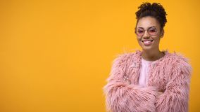 Nowożytna młoda kobieta pozuje na kamery żółtym tle, stylowi kursy, szablon zdjęcia royalty free