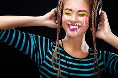 Nowożytna młoda kobieta z sztuki makeup cieszy się słuchanie muzyka w hełmofonach Pozytywne emocje, czas wolny kosmos kopii Obraz Royalty Free