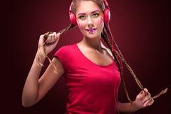 Nowożytna młoda kobieta z sztuki makeup cieszy się słuchanie muzyka wewnątrz Fotografia Royalty Free