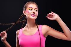 Nowożytna młoda kobieta z sztuki makeup cieszy się słuchanie muzyka wewnątrz Fotografia Stock