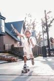 Nowożytna mała dziewczynka jest ubranym małą koronę jeździć na deskorolce blisko jej domu obraz royalty free