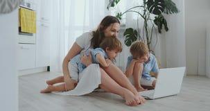 Nowożytna mieszkanie mama i dwa syna siedzi na podłodze w żywym izbowym spojrzeniu przy laptopu ekranem zbiory