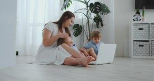 Nowożytna mieszkanie mama i dwa syna siedzi na podłodze w żywym izbowym spojrzeniu przy laptopu ekranem zdjęcie wideo