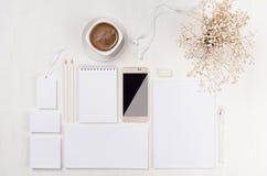 Nowożytna minimalistic elegancka kobieca pracy przestrzeń z białym pustym materiały, kawa, kwiaty, telefon na białej drewno desce zdjęcia royalty free