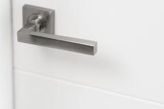 Nowożytna srebna drzwiowa rękojeść na białym drzwi Zdjęcie Royalty Free