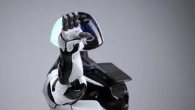Nowożytne mechaniczne technologie Biały nowożytny robot w jaskrawym studiu Android macha powitanie rękę, wita widza zbiory wideo