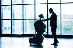 Nowożytne mechaniczne technologie Mężczyzna komunikuje z robotem, naciska plastikową machinalną rękę robot, uścisk dłoni Obrazy Stock
