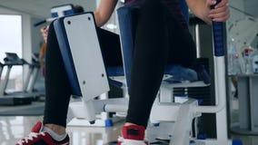 Nowożytne technologie w sportach, kobieta robi ćwiczenia rozszerzenia obsiadaniu w centrum sportowe zdjęcie wideo