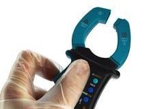Nowożytnego kahata elektryczny multimeter trzymający w lewej ręce w przejrzystej lateksowej rękawiczce, biały tło obraz royalty free