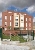 Nowożytnego mieszkania pomarańczowa ceglana fasada z ogrodzeniem. Obraz Stock
