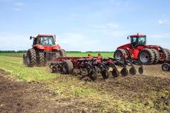 Nowożytnej techniki czerwony ciągnik orze zielonego rolniczego pole w wiośnie na gospodarstwie rolnym Żniwiarz wysiewna banatka Obraz Stock