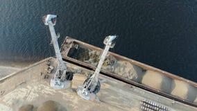 Nowożytni żurawie pracują przy dokami, poruszający breakstones od barki zbiory