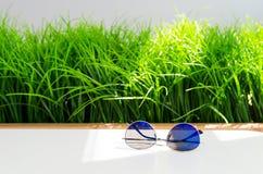 Nowożytni błękitni okulary przeciwsłoneczni na bielu stole na jaskrawym - zielonej trawy tło z kopii przestrzenią fotografia royalty free