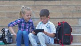 Nowożytni mali ucznie używają gadżetu obsiadanie na krokach szkoła z plecakami w na wolnym powietrzu podczas recesji