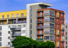 Nowożytni mieszkania z białymi, żółtymi i czerwonymi colours za drzewami, obrazy royalty free