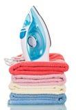 Nowożytni parowego żelaza i sterty ręczniki odizolowywający na bielu zdjęcie royalty free