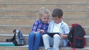 Nowożytni schoolkids, mała dziewczynka i mała chłopiec, używają cyfrowego pastylki obsiadanie na krokach blisko plecaków podczas