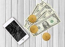 Nowożytny łamający telefon komórkowy i dolary na biały drewnianym Zdjęcia Royalty Free