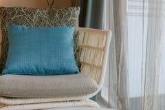 Nowożytny łozinowy krzesło z poduszką i wygody poduszka w pokoju Blisko okno obraz royalty free