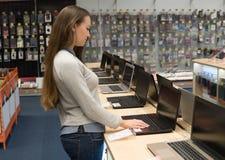 Nowożytny żeński klient wybiera laptop w komputerowym sklepie fotografia royalty free