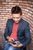 Nowożytny Azjatycki mężczyzna Używa Cyfrowej pastylkę w biurze fotografia stock