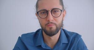 Nowożytny biznesmen z ponytail i eyeglasses ono uśmiecha się joyfully w kamerę odizolowywającą na białym tle zdjęcie wideo