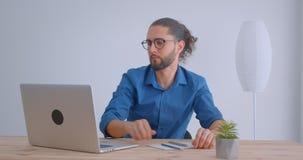 Nowożytny biznesmen z ponytail i eyeglasses pracuje z laptopem i robi notatkom w białym biurze attentively zdjęcie wideo
