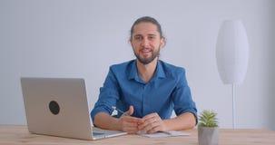 Nowożytny biznesmen z ponytail ono uśmiecha się w kamerę jest radosny bawić się z ołówkiem w białym biurze zdjęcie wideo
