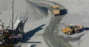 Nowożytny buldożer pracuje w karierze, buldożeru ładunków pomarańczowi kamienie w usyp ciężarówkę zbiory wideo