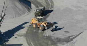 Nowożytny buldożer pracuje w karierze, buldożeru ładunków pomarańczowi kamienie w usyp ciężarówkę zdjęcie wideo