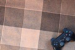 Nowożytny czarny wideo gry kontroler kłama na w kratkę czerni szkocka krata, beżu lub przesłona i Plastikowy joystick jako pojęci obrazy royalty free